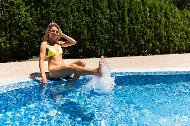フルショットの女性がプールでポーズ