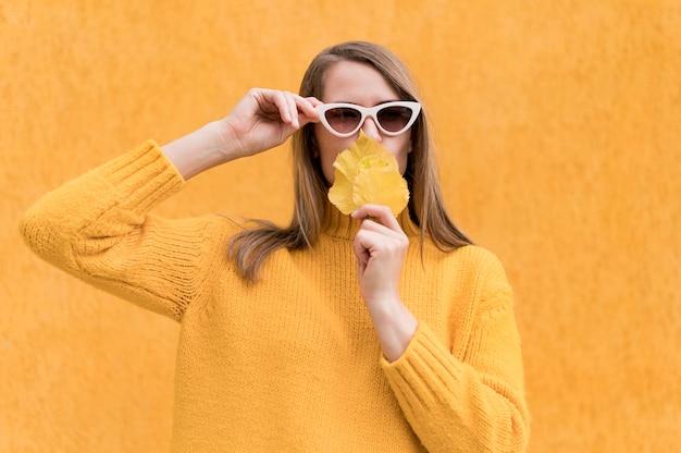 黄色の葉で彼女の口を覆っている女性