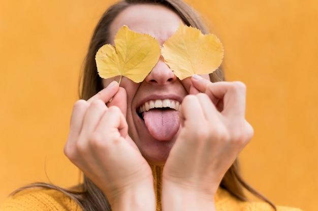 黄色の葉で目を覆っている女性