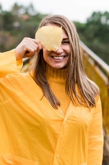 屋外の雨の服を着て正面女性