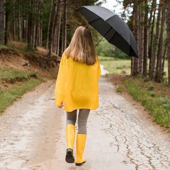 Вид сзади женщина на прогулке в лесу