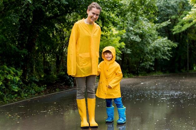 ロングショットの母と息子が雨が降っている間手を繋いで