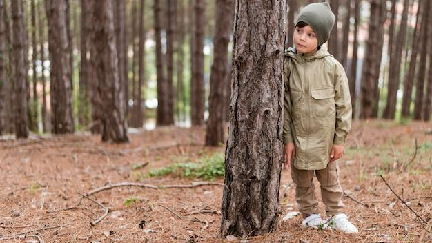 コピースペースを持つ木の隣に立っている小さな男の子の正面図