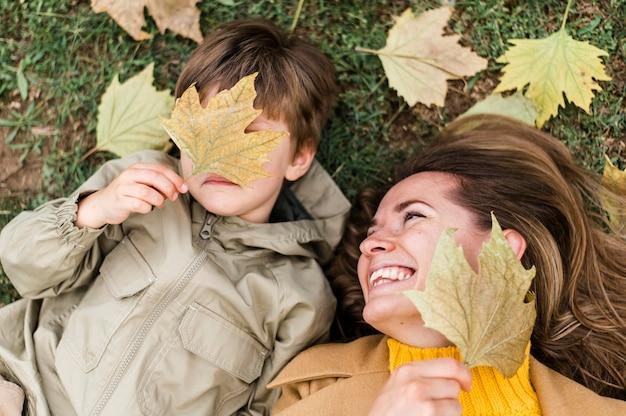 トップビューの小さな男の子と秋の紅葉と遊ぶ母