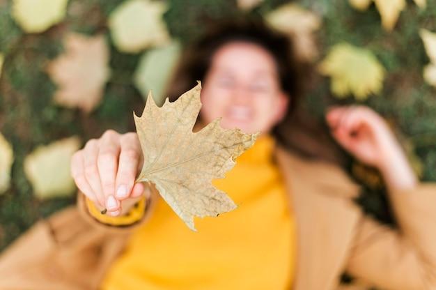 葉を押しながら地面に滞在しているトップビュースマイリー女性