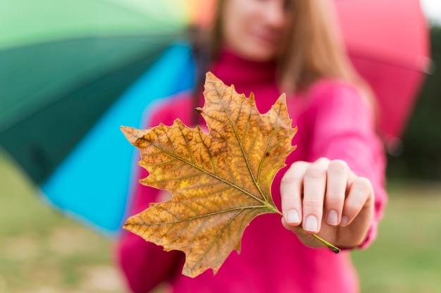 Женщина с красочным зонтиком держит осенний лист