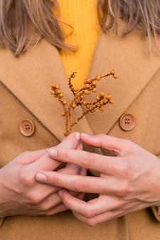 彼女の胸に植物を保持している女性
