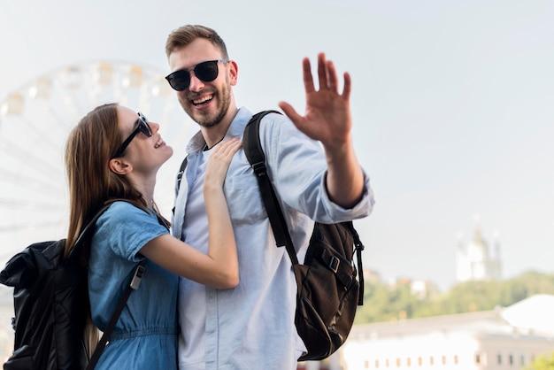 手を振っている人と観光客カップル