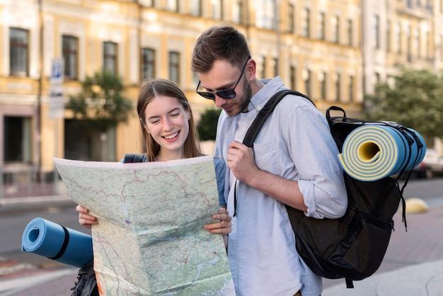 バックパックを運んでいる間地図を保持している観光客のカップル