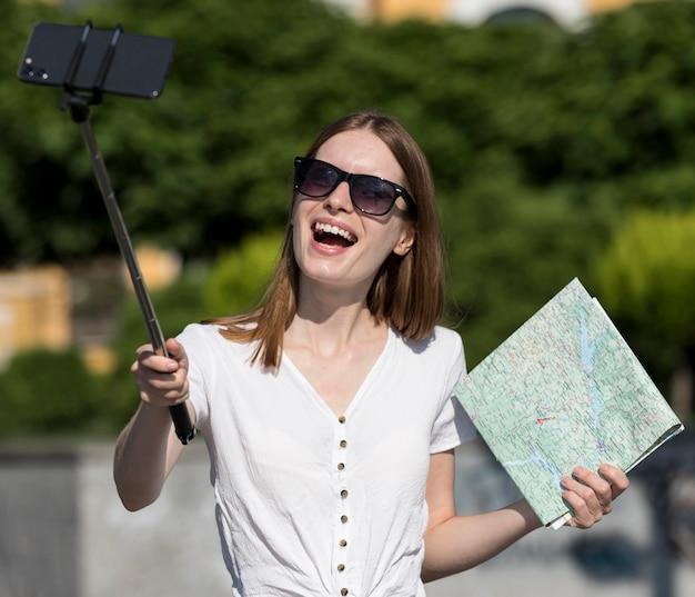 Улыбающаяся туристическая женщина, держащая карту и делающая селфи