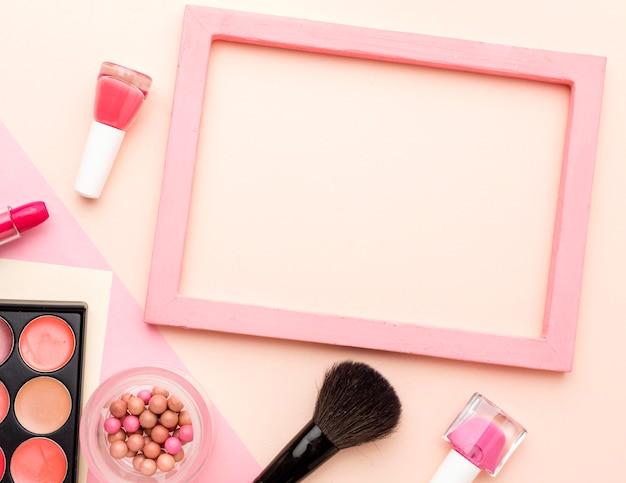 Рамка сверху, окруженная аксессуарами для макияжа