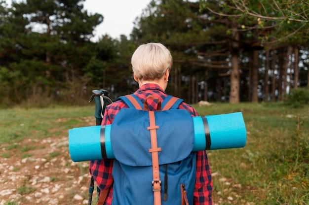 Задний взгляд старшей туристской женщины в природе