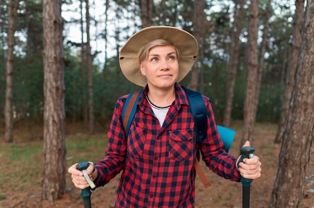 Вид спереди старшей туристической женщины в лесу