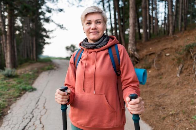 Улыбающаяся старшая туристская женщина с походными палками в лесу