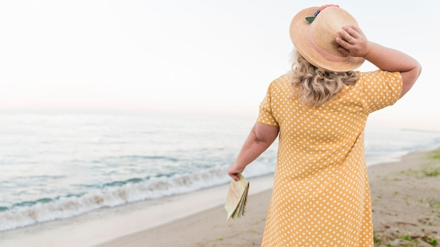 Вид сзади старшая туристическая женщина на пляже