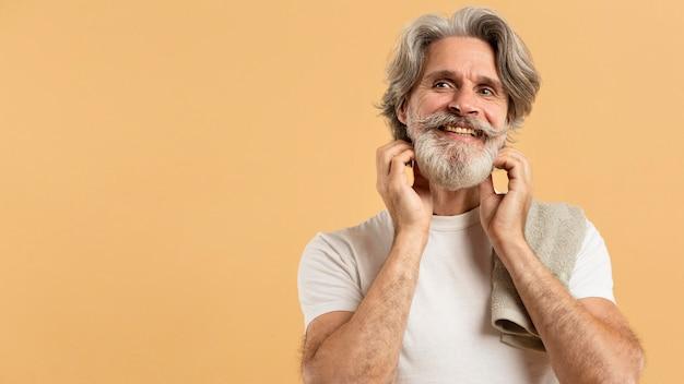 Вид спереди старшего мужчины с бородой и полотенцем