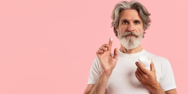 Вид спереди старшего человека с бородой, держа крем