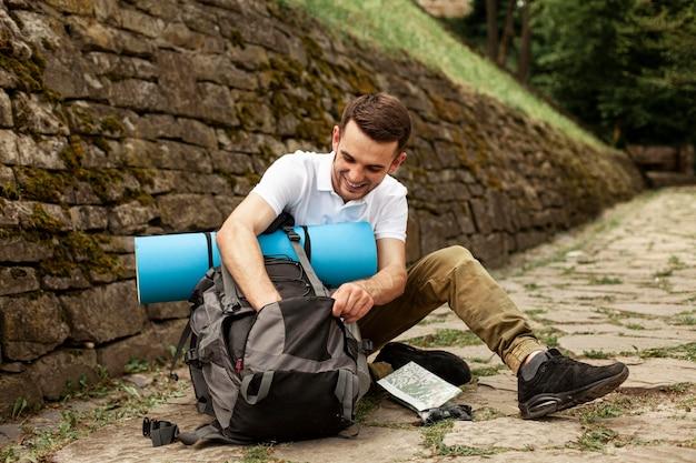彼のバックパックを作る旅行者