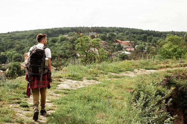 Портрет мужчины с рюкзаком на дороге