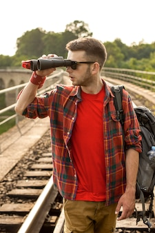 距離に双眼鏡で見ているバックパックを持つ男