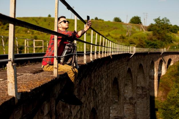 Человек сидит на краю моста и принимая селфи