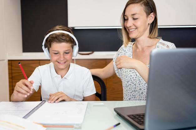 母親が息子の宿題を終えるのを手伝う