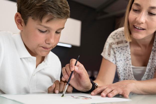 母親が息子が絵を描くのを手伝う