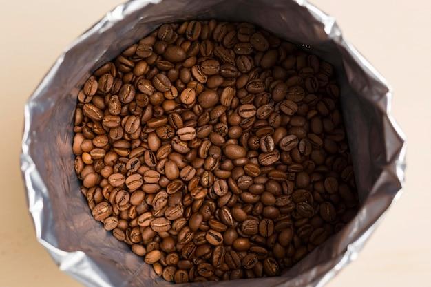 ベージュ色の背景にブラックコーヒー豆