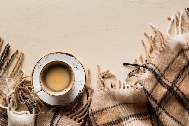 コピースペースとベージュ色の背景上のコーヒーのトップビューカップ
