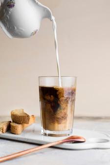 Вид спереди наливают молоко в фраппе рядом с кусочками хлеба с семечками