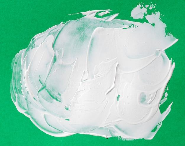 Белый мазок кисти на зеленом фоне