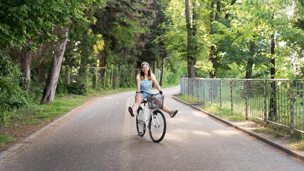 Красивая молодая девушка езда на велосипеде на открытом воздухе