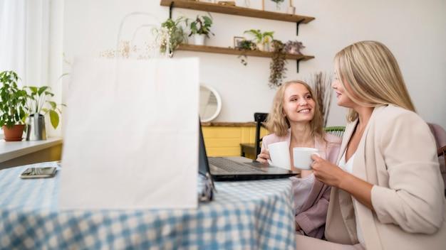 Стильные взрослые женщины, делающие покупки онлайн