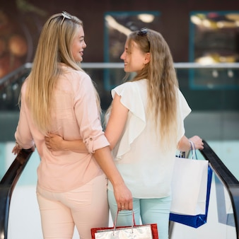 背面ビューのエレガントな女性が一緒に買い物に満足
