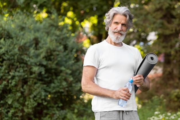 Мужчина среднего роста с ковриком для йоги и водой