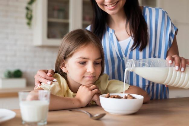 Крупным планом мать разлива молока в миску