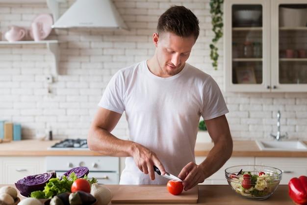 Человек среднего размера, режущий помидор