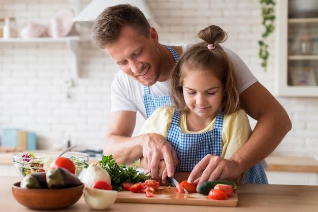 Вид спереди папа приготовления пищи с дочерью