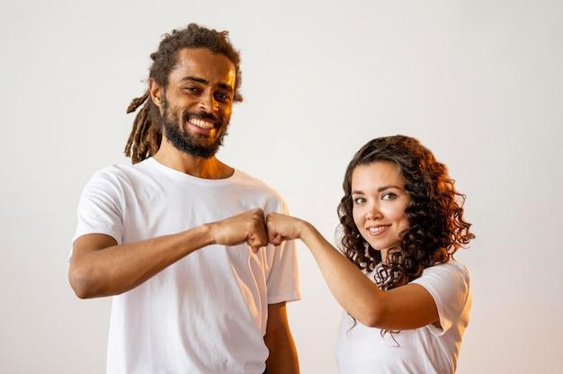 Разные расовые люди сталкиваются кулаками