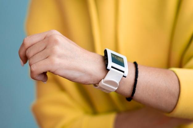スマートな時計のクローズアップを着ている女性