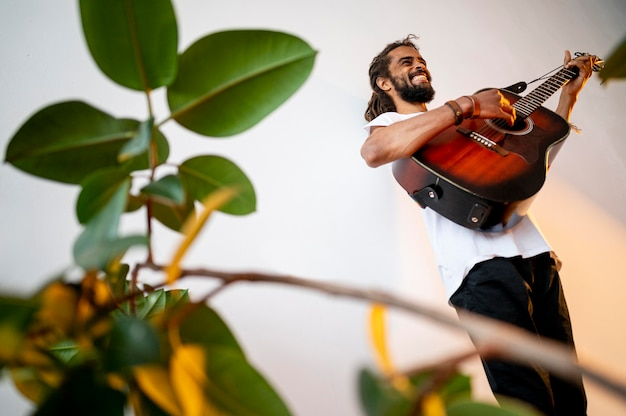 コピースペースで室内でギターを弾く男