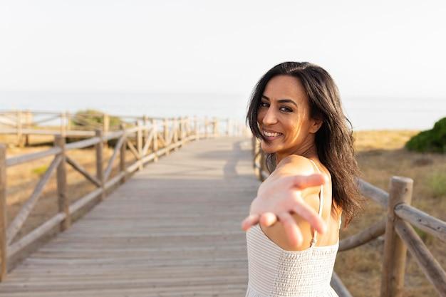 手を伸ばして屋外でポーズ笑顔の女性の側面図