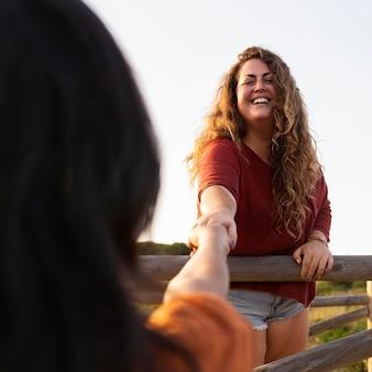 スマイリー女性が友達と屋外でポーズ