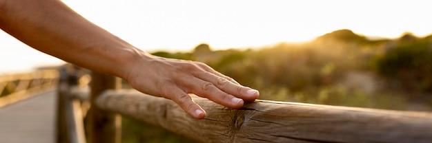 屋外の木製のフェンスに触れる手