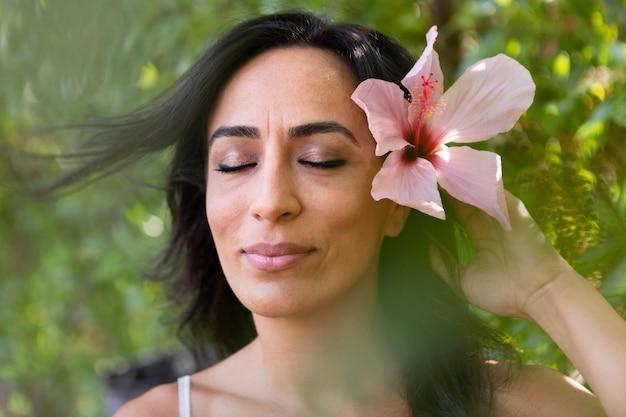 屋外の髪に花を持つ美しい女性の正面図