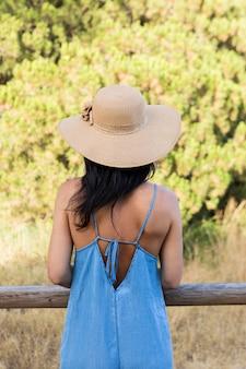 木製のフェンスにもたれながら屋外でポーズの女性の背面図