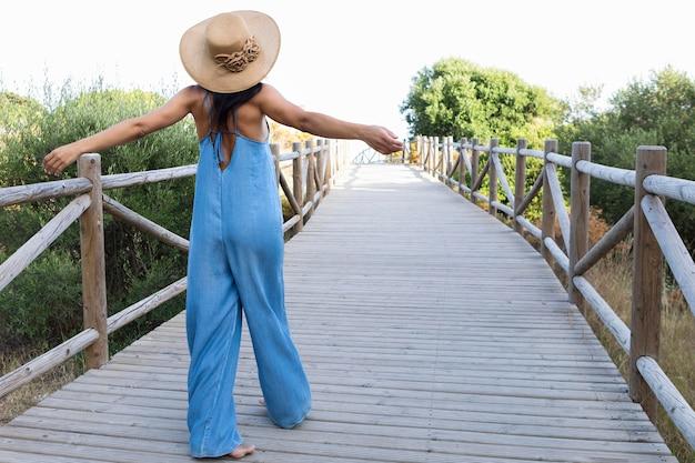Вид сзади женщины на мосту на улице с шляпой на