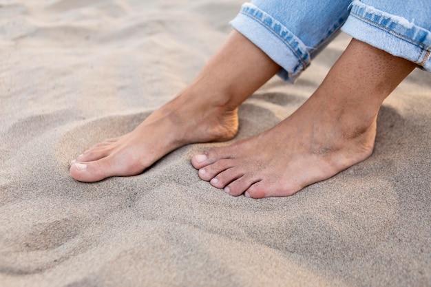 ビーチで砂の中の女性の足