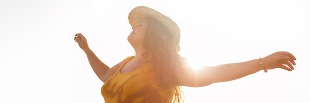 太陽の下で屋外の屈託のない女性の側面図
