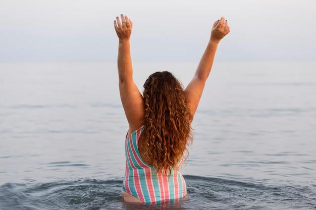 ビーチで水の中の女性の背面図